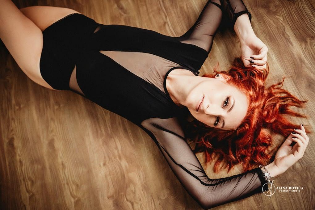 femeie întinsă pe jos fotografiata de sus, poze boudoir, body negru cu mâneca lunga, Body tulle negru, par roșu, par roșcat,