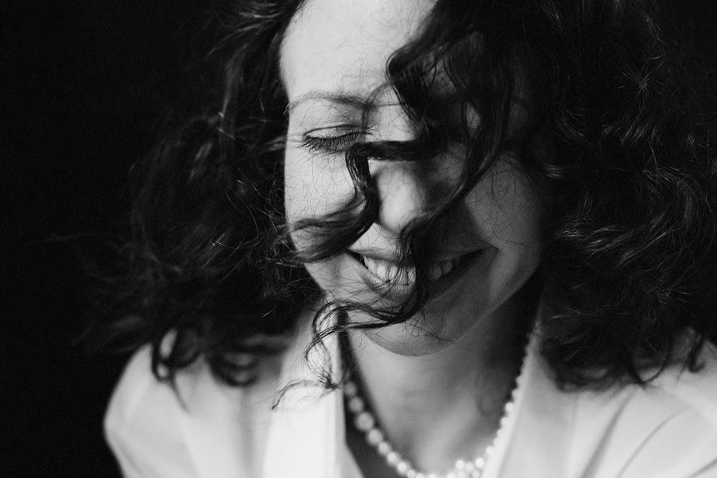 femeie cu parul în vânt râzând fotografie alb negru alina Botica RawYou Diana Cosmin Finesociety